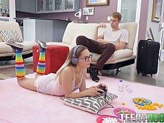 Девушка в очках лежа на животе занимается сексом не отрываясь от игры в приставку