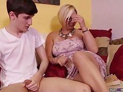 Busty blonde milf is jerking off a younger dude, to show him...