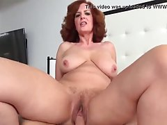 Mature redhead is squeezing her saggy tits and riding a hard...