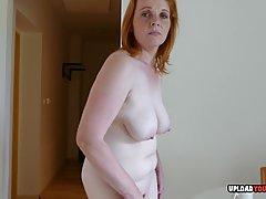 Рыжая зрелая женщина уверенно показывает в камеру упругое вл...