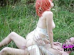 Рыжая девушка в униформе супер героини на природе трусит большими сиськами