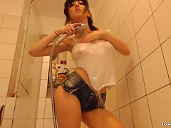 Kinky girl is getting a huge dildo which is affixed on a wall in her bathroom